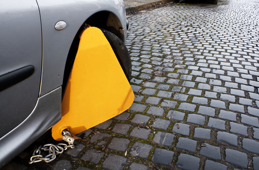 Car with clamp on to immobilize movement as a penalty to an offence such as no tax