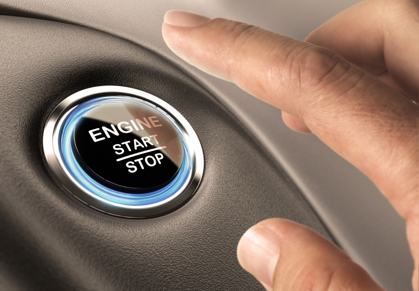 Car engine start and stop button with blue light and black textured background, close up and one finger